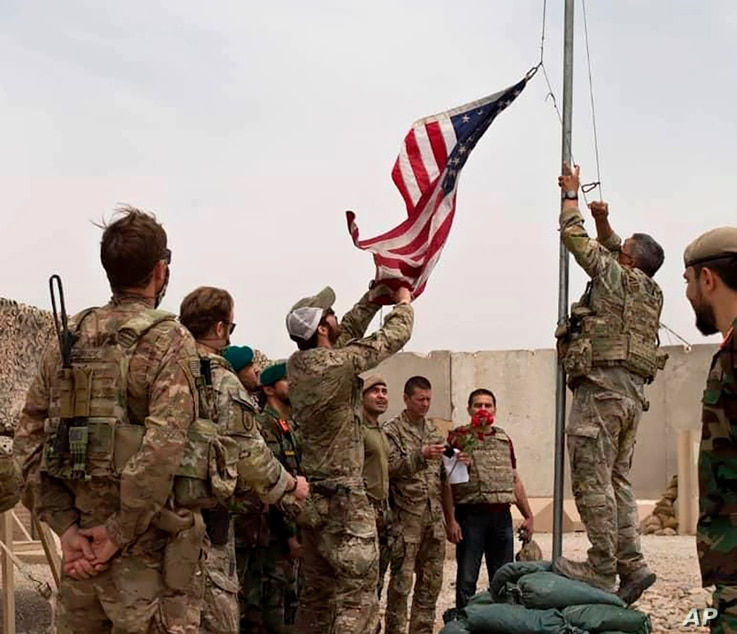 A U.S. flag is lowered as American and Afghan soldiers attend a handover ceremony from the U.S. Army to the Afghan army.
