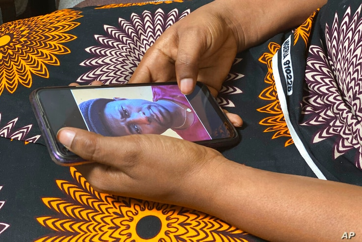 Anifa holds her phone displaying a photo of former World Health Organization doctor Boubacar Diallo, of Canada, during an…