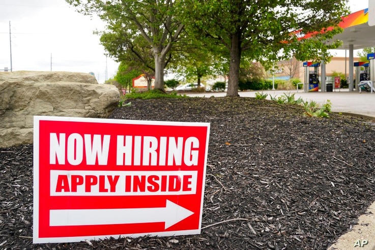 Hiring signs are posted outside a gas station in Cranberry Township, Butler County, Pa., Wednesday, May 5, 2021.  The U.S…