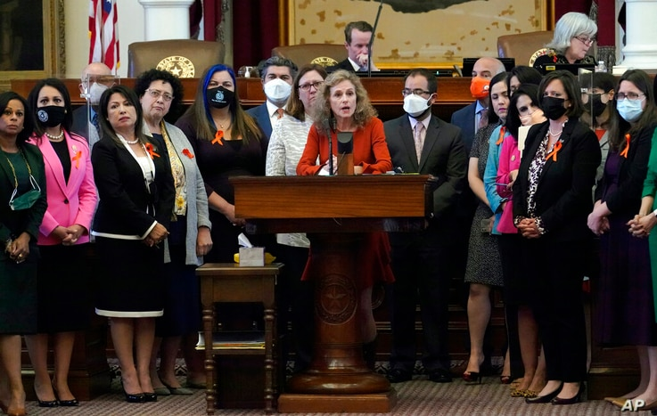 Texas state Rep. Donna Howard, D-Austin, center at lectern, stands with fellow lawmakers in the House Chamber, Wednesday, May 5…