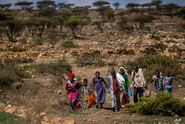 People walk from a rural area toward a nearby town where a food distribution operated by the Relief Society of Tigray was…