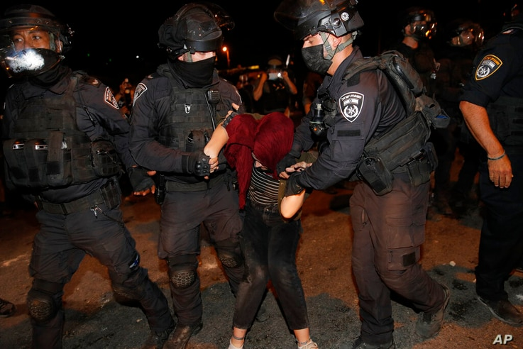Israeli police officers detain a Palestinian demonstrator during a protest against the planned evictions of Palestinian…