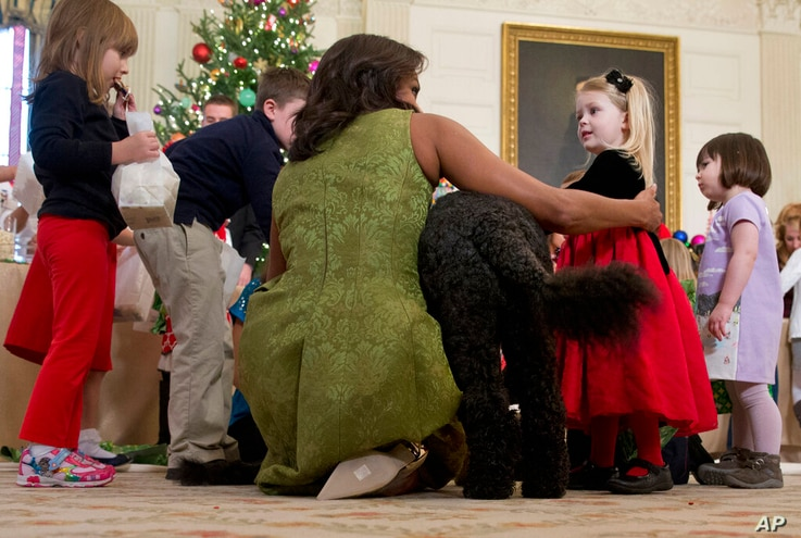 FILE - In this Dec. 2, 2015, file photo first lady Michelle Obama, with dog Bo is surrounded by children in the State Dining…