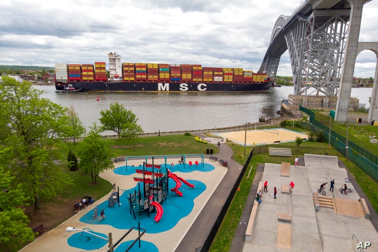On the way to the Port of New York and New Jersey, a container ship passes by a playground and a skateboard park at the Bayonne...