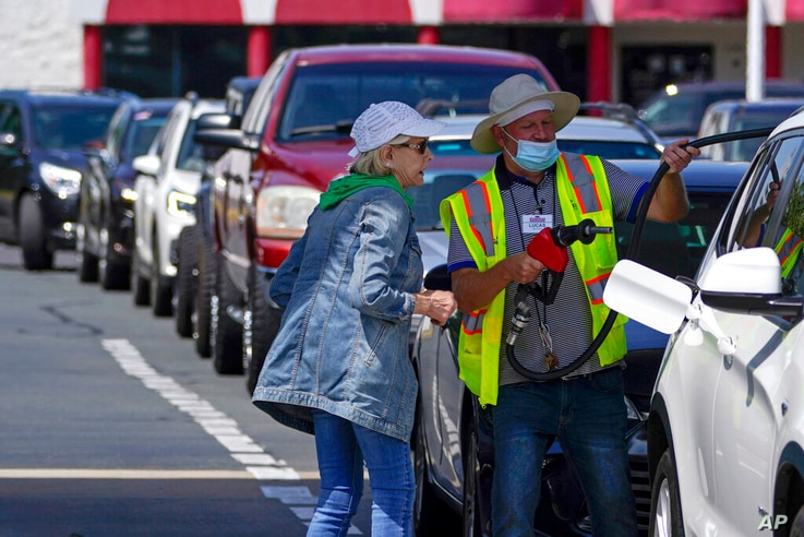 A customer helps pumping gas at Costco, as other wait in line, on Tuesday, May 11, 2021, in Charlotte, N.C. Colonial Pipeline,...