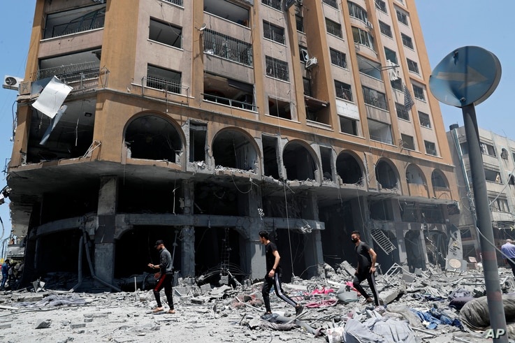 People inspect the rubble of a damaged building which was hit by an Israeli airstrike, in Gaza City, May 12, 2021.