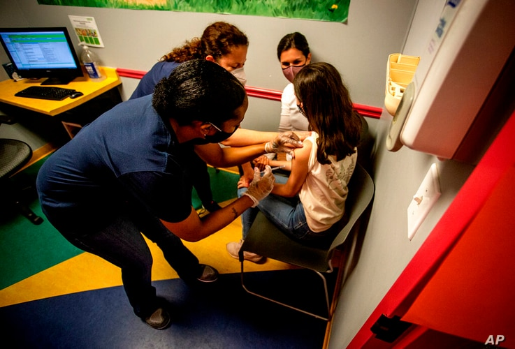 Middle school student Elise Robinson receives her first coronavirus vaccination on Wednesday, May 12, 2021, in Decatur, Ga…