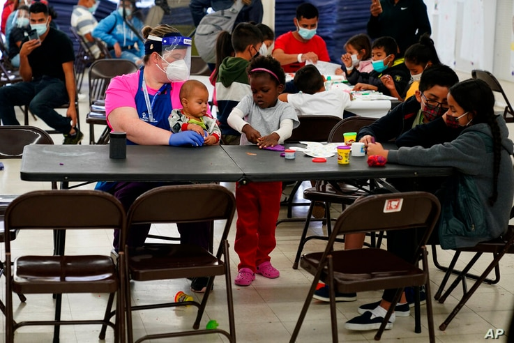 Migrants pass the time at a migrant shelter, Wednesday, May 12, 2021, in McAllen, Texas. The U.S. government continues to…
