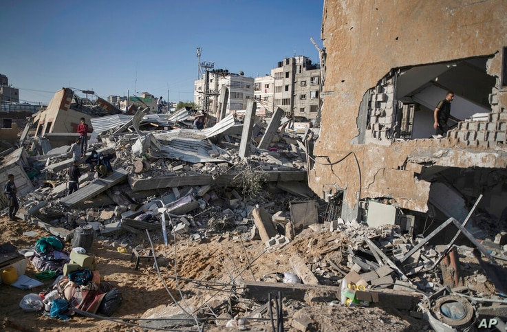 Palestinians inspect the rubble of their destroyed homes after being hit by Israeli airstrikes in town of Beit Lahiya, northern...