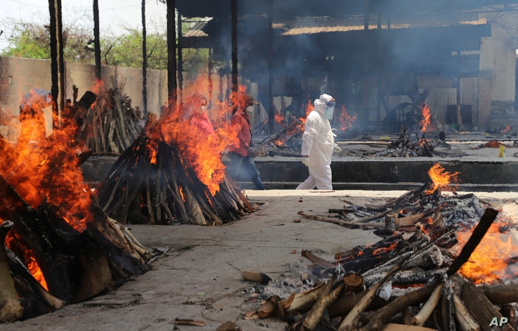 Multiple funeral pyres of people who died of COVID-19 burn at the Ghazipur crematorium in New Delhi, India.