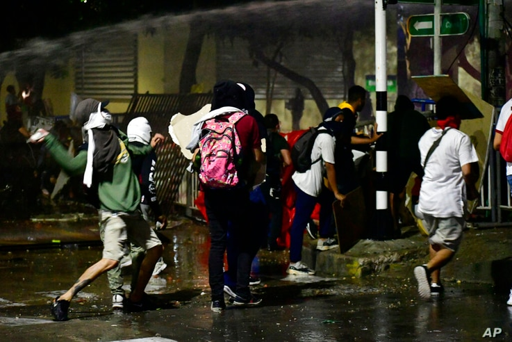Anti-government protesters clash with police near Romelio Martinez stadium where a Copa Libertadores soccer match between…