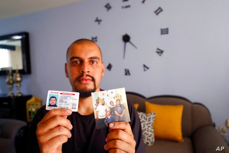 Jesus Lopez, who was deported from the U.S. last year, holds up his Illinois driver's license and a family snapshot, at his…