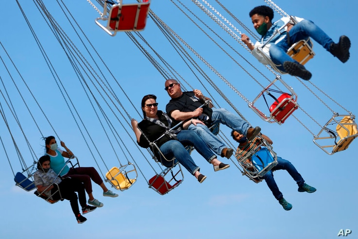 People enjoy their time in a wave swinger Friday, May 14, 2021 at Chicago's Navy Pier. The U.S. Centers for Disease Control and…