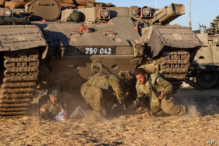 Israeli soldiers take cover under armored vehicles as a siren sounds warning of incoming rockets fired from Gaza strip in a…