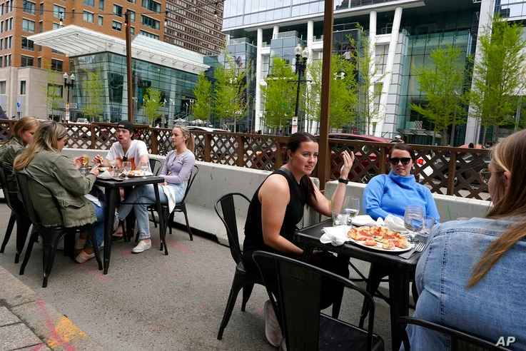 FILE - In this Sunday, May 2, 2021 file photo, patrons seated at outdoor tables at a restaurant converse and dine without masks…
