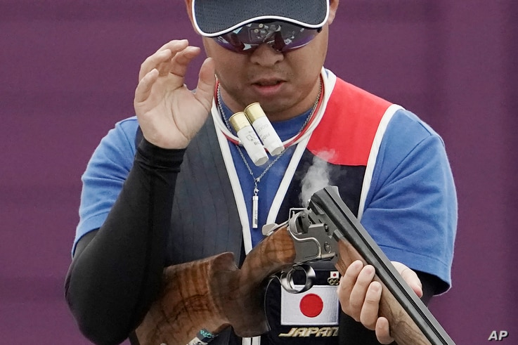 Hiroyuki Ikawa ejects spent cartridge shells as he competes in thew skeet shooting competition of the Tokyo 2020 Olympic Game…