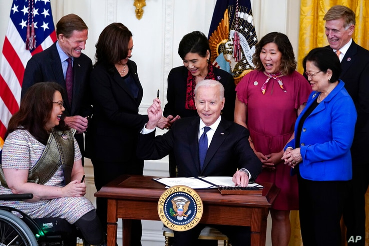 President Joe Biden hands out a pen after signing the COVID-19 Hate Crimes Act, in the East Room of the White House, Thursday,…