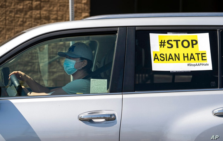 FILE — In this March 19, 2021, file photo, members of the Korean American Federation of Los Angeles drive with signs reading: '...