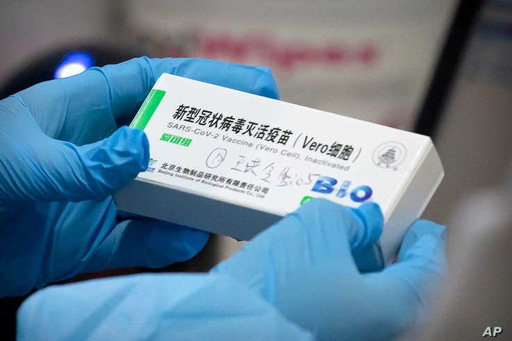FILE - A medical worker holds a package for a Sinopharm vaccine at a vaccination facility in Beijing, Jan. 15, 2021.