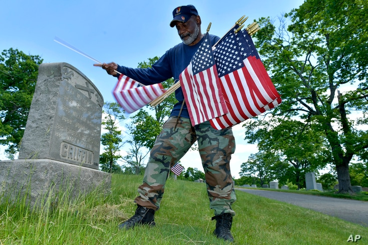 Bob Workman of Boston, a retired Marine Gunnery Sgt., and past commander of the Boston Police VFW, replaces flags.