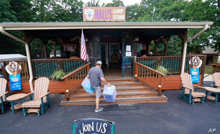 Mike Bond carries boxes as he prepares for the expected Memorial Day weekend visitors to Hall's Camp Store at the Vineyard…
