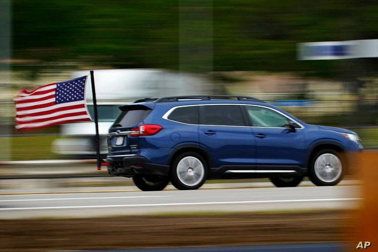 A motorist from Massachusetts flies an American flag ahead of the Memorial Day holiday while traveling on the Maine Turnpike,…