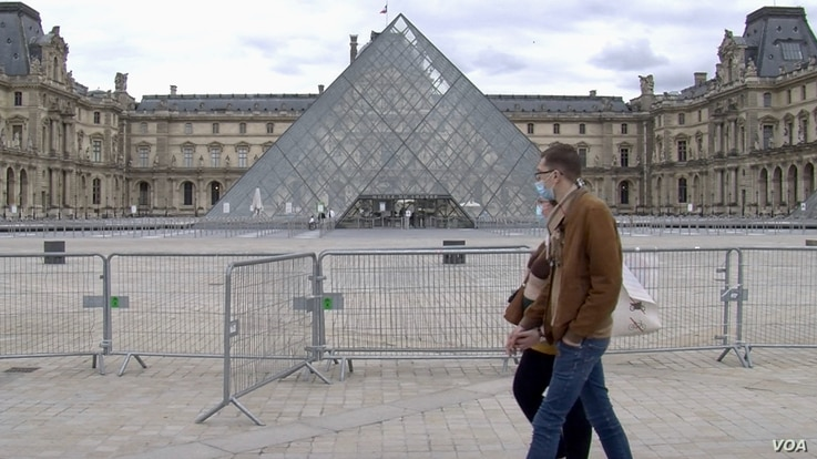 Parisians walk past the Louvre Museum which will soon be open to visitors. (Lisa Bryant/VOA)