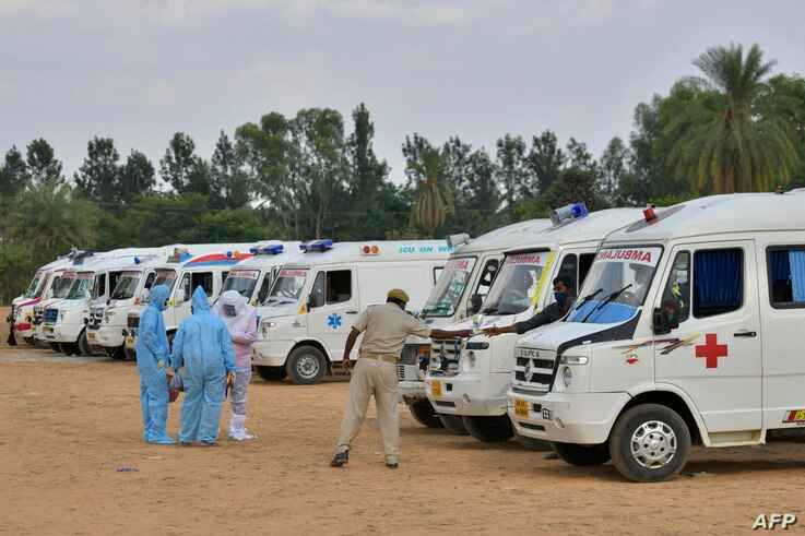 Family members wearing protective gear stand next to ambulances carrying bodies of COVID victims, at an open air cremation site set up on the outskirts of Bangalore, India, May 8, 2021.