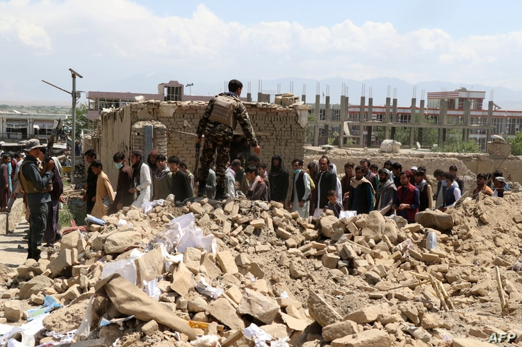 Security personnel and residents gather at the site of a car bomb attack in the Pul-e-Alam area of Logar province, Afghanistan, May 1, 2021.