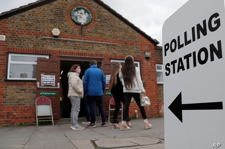 People queue at the entrance of a polling station in London, May 6, 2021. Millions of people across Britain cast ballots Thursday, in local elections, the biggest set of votes since the 2019 general election.
