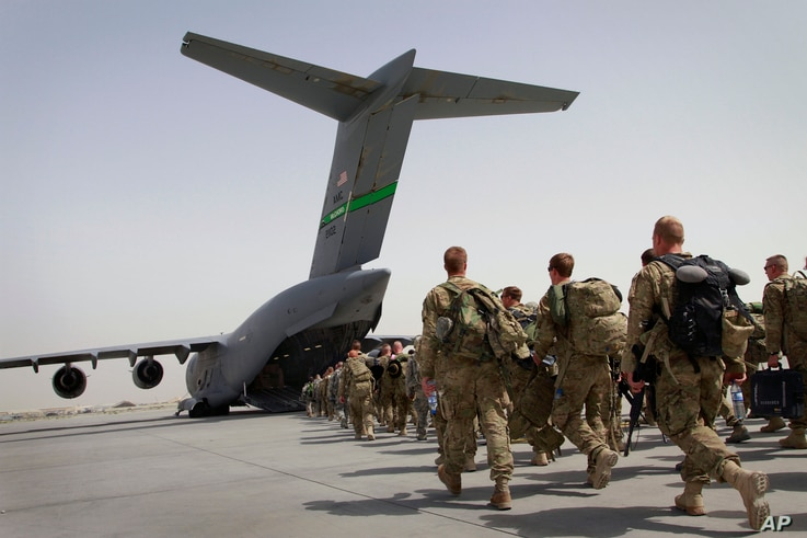 FILE - U.S. soldiers load onto a U.S. military plane as they leave Afghanistan, at the U.S. base in Bagram, north of Kabul, Afghanistan, July 14, 2011.