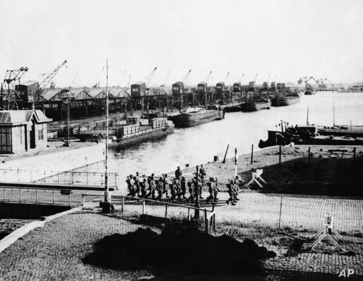 FILE - British troops march past undamaged port facilities in Antwerp, Nov. 15, 1944 before mounting guard over the dock area of the important Belgium port.