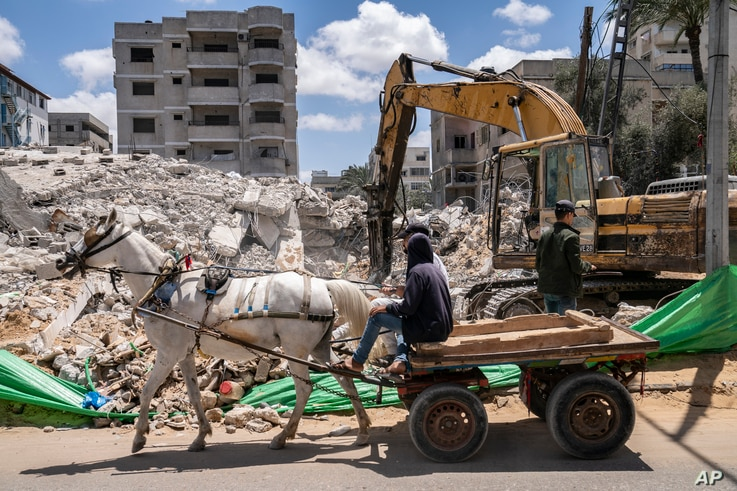 A horse-drawn cart passes a worker using an excavator to dig through debris of a building destroyed by an airstrike prior to a cease-fire reached after an 11-day war between Gaza's Hamas rulers and Israel, in Gaza City, May 22, 2021.