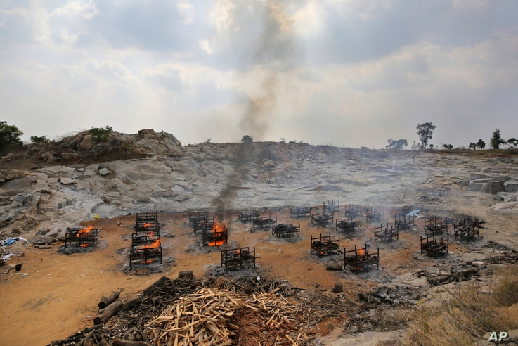 Funeral pyres of 25 COVID-19 victims burn at an open crematorium on the outskirts of Bengaluru, India, May 5, 2021.