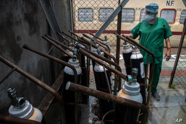A health worker checks oxygen cylinders stored next to a train at a railway station in Gauhati, India, May 6, 2021.