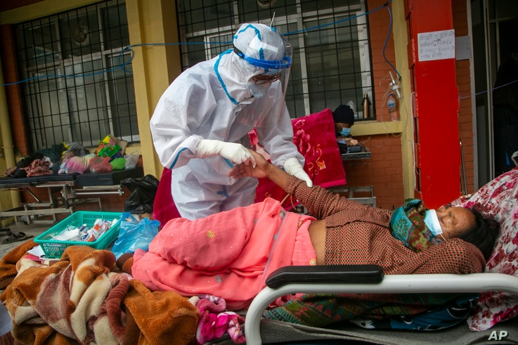 Nepalese paramedics treat a COVID-19 patient outside an emergency ward of a government-run hospital in Kathmandu, Nepal, May 10, 2021.