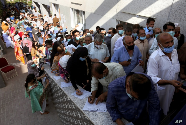 People queue to receive the first shot of the Sinopharm COVID-19 vaccine at a vaccination center in Karachi, Pakistan, May 8, 2021.