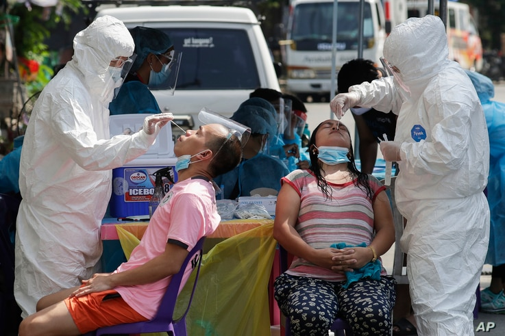 Health workers conduct a COVID-19 swab test on residents at a village in Quezon City, Philippines.