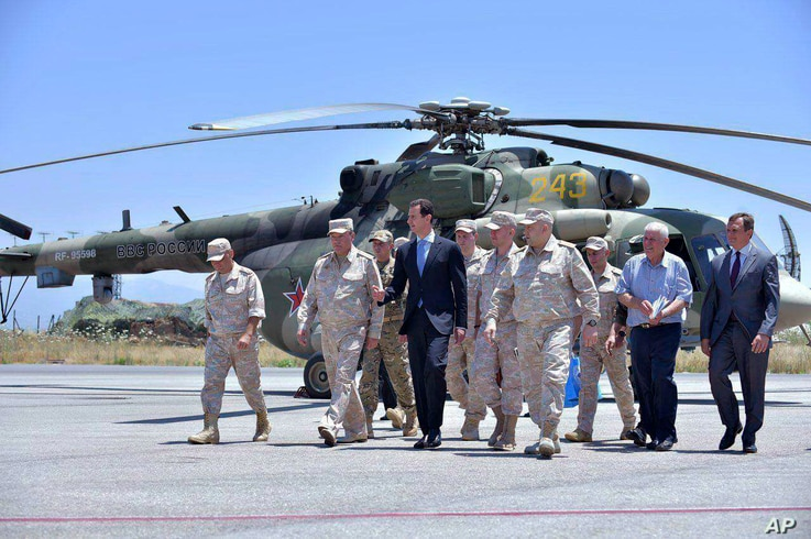 FILE - Syrian President Bashar Assad inspects the Russian Hmeimim air base in the province of Latakia, Syria, June 27, 2017.