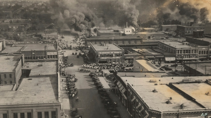 FILE - This photo provided by the Department of Special Collections, McFarlin Library, University of Tulsa shows crowds of people watching the fires during the Tulsa Race Massacre in Tulsa, Oklahoma on June 1, 1921.