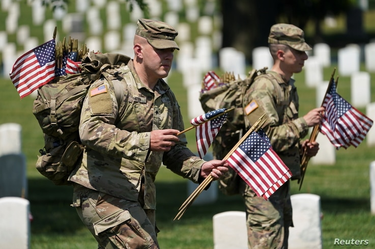 Ahead of Memorial Day, members of the U.S. armed forces place flags in front of more than 260,000 headstones at Arlington National Cemetery, in Arlington, Virginia, May 27, 2021.