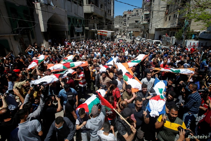 Mourners carry the bodies of Palestinians who were killed amid a flare-up of Israeli-Palestinian violence, during their funeral at the Beach refugee camp, in Gaza City, May 15, 2021.