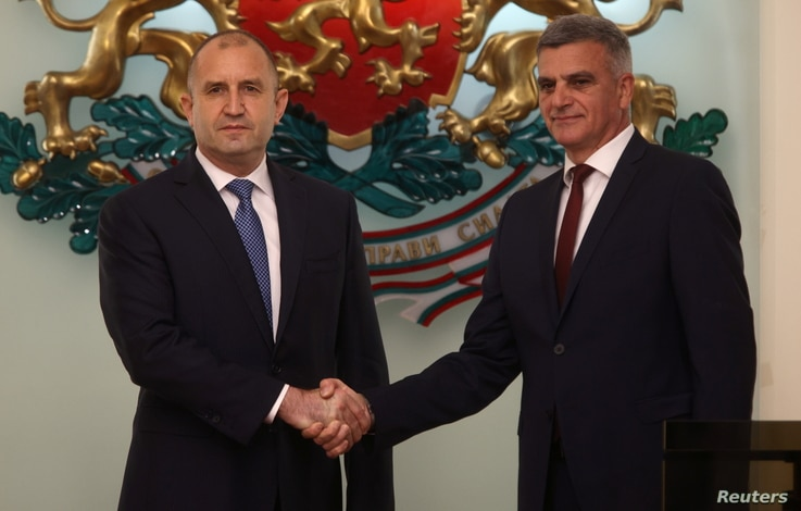 Newly-appointed caretaker Prime Minister Stefan Yanev, left, shakes hands with Bulgaria's President Rumen Radev during an official ceremony in Sofia, Bulgaria, May 12, 2021.