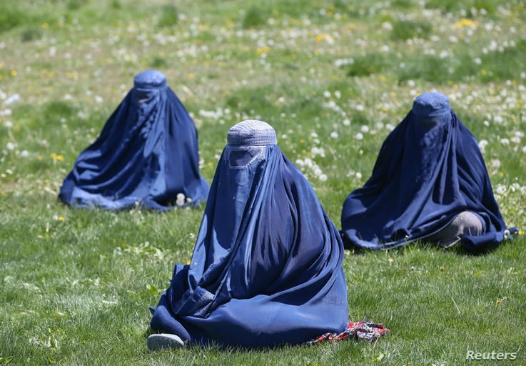 Afghan women wait to receive free wheat donated by the government during a quarantine, amid concerns about the COVID-19 in Kabul, April 21, 2020.