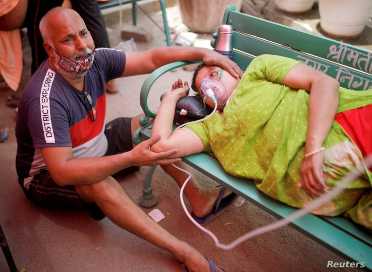 Mukesh Bhardwaj cries next to his wife, who receives oxygen support outside a Gurudwara (Sikh temple) in Ghaziabad, India, May 3, 2021.