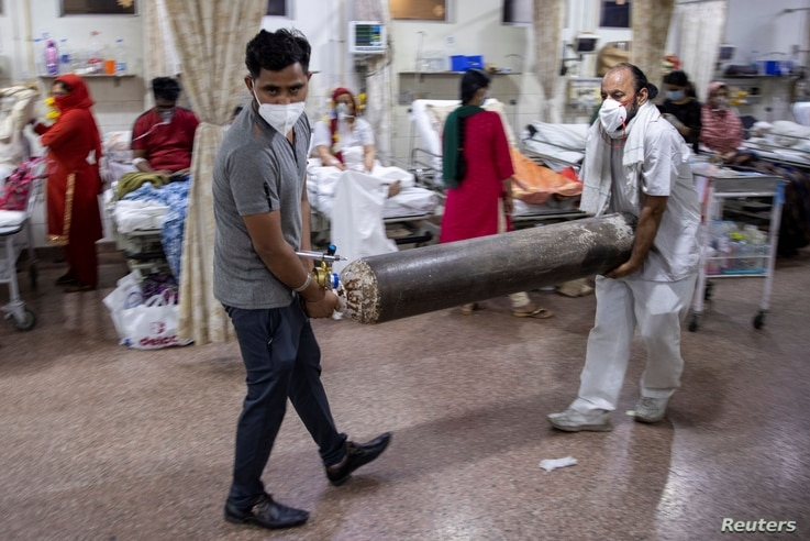 Relatives of a woman suffering from the COVID-19, carry an oxygen cylinder as she receives treatment in the emergency room of Holy Family Hospital in New Delhi, India, May 1, 2021.
