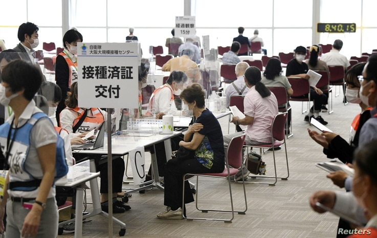 Senior citizens wait to receive a COVID-19 vaccine at a large-scale vaccination center in Osaka, western Japan, May 24, 2021, in this photo distributed by Kyodo.