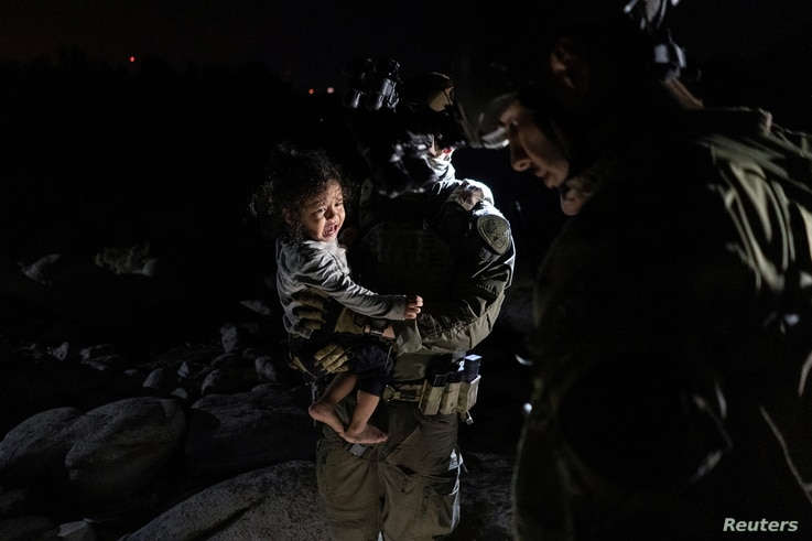 An asylum-seeking migrant girl is carried by a Department of Public Safety agent while her mother is disembarking from an inflatable raft after crossing the Rio Grande river into the United States from Mexico in Roma, Texas, May 5, 2021.