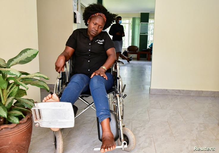 FILE - Irene Abalo, a journalist working with The Daily Monitor newspaper, sits on a wheelchair after she was injured in an attack by security officials, outside the UN Human Rights offices while on reporting duty, in Kampala, Uganda Feb. 17, 2021.