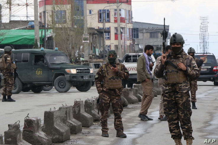 Afghan security personnel stand guard near the site of an attack to a Sikh temple in Kabul on March 25, 2020. - The Islamic…